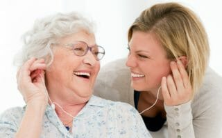 Excited grandmother listening music together with her granddaugh