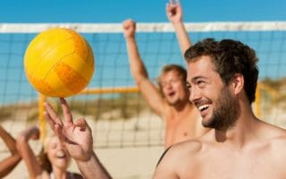 Group of friends - women and men - playing beach volleyball, one