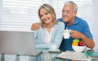 Happy couple using laptop while having breakfast