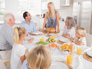 Family looking at the mother with a turkey plate for dinner