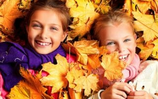 Portrait of two cute girls sisters lying on the leaves at the au