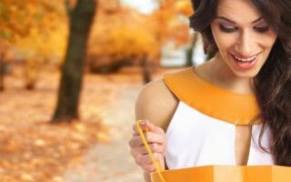 Young beautiful woman with some shopping bag over autumn backgro