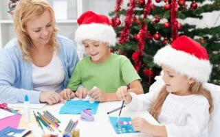 Family around christmas time making greeting cards wearing santa
