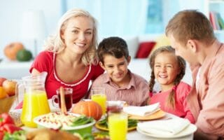 Portrait of happy family gathered at festive table on Thanksgivi