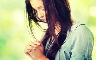 Closeup portrait of a young caucasian woman praying, against abs