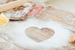 cooking and love concept - close up of heart of flour on wooden
