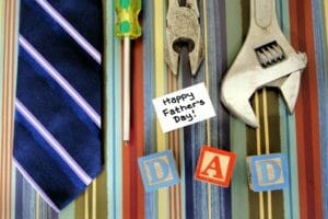 Father's day on colorful background. Ties, wrenches, screwdriver's and child blocks that spell the word dad.