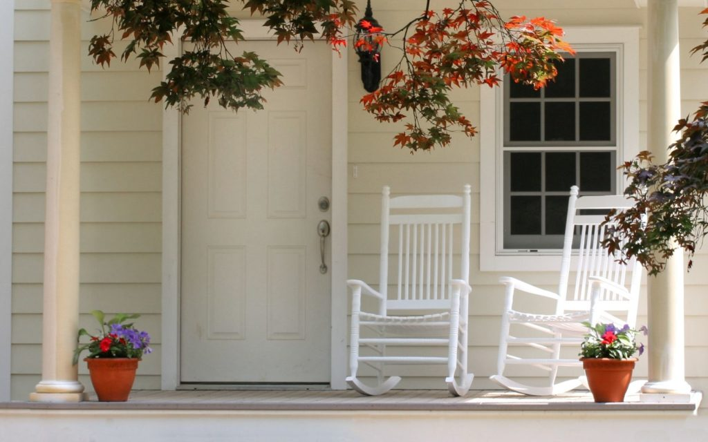 Pair of white rocking chairs sitting on a porch