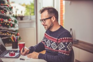 Man writing a Christmas letter.