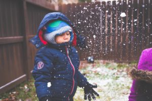 Christmas tradition: backyard camping. Little boy in winter coat, enjoying snow in the backyard.