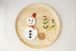 Christmas breakfast snowman pancake with kiwi fruit Christmas trees.