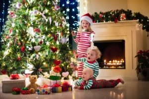 Little children in front of a christmas tree in matching pajamas.