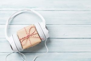 Christmas music gift concept. Headphones and gift box on wooden table. Listen to Christmas music each morning.